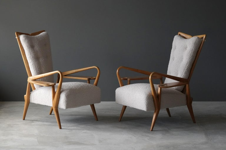 A pair of highly modernist and organic lounge chairs / highback chairs in finely carved maple, reupholsted in off white bouclé. Design attributed to Giordano Forti. Produced in Italy in the 1940s. The design incorporates side tables built onto the