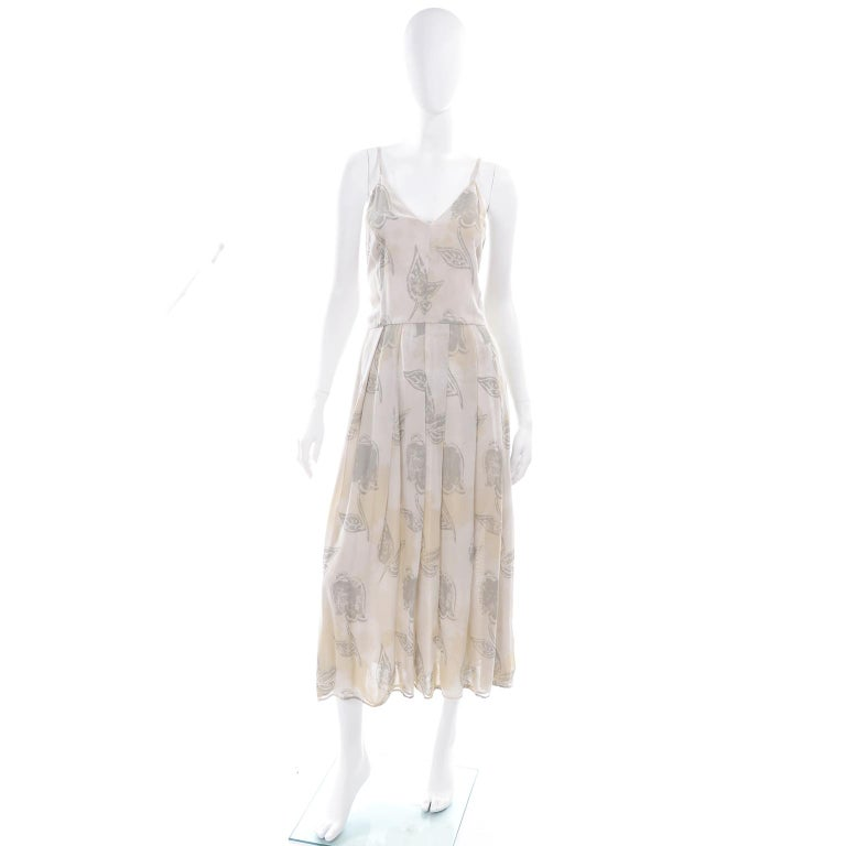 This is a unique vintage Giorgio Armani pale khaki cream and sage green dress in a pattern that has abstract leaves and purposeful color layover that almost looks like tea staining. This dress has a V-neck in front and a V in back, a pleated skirt,