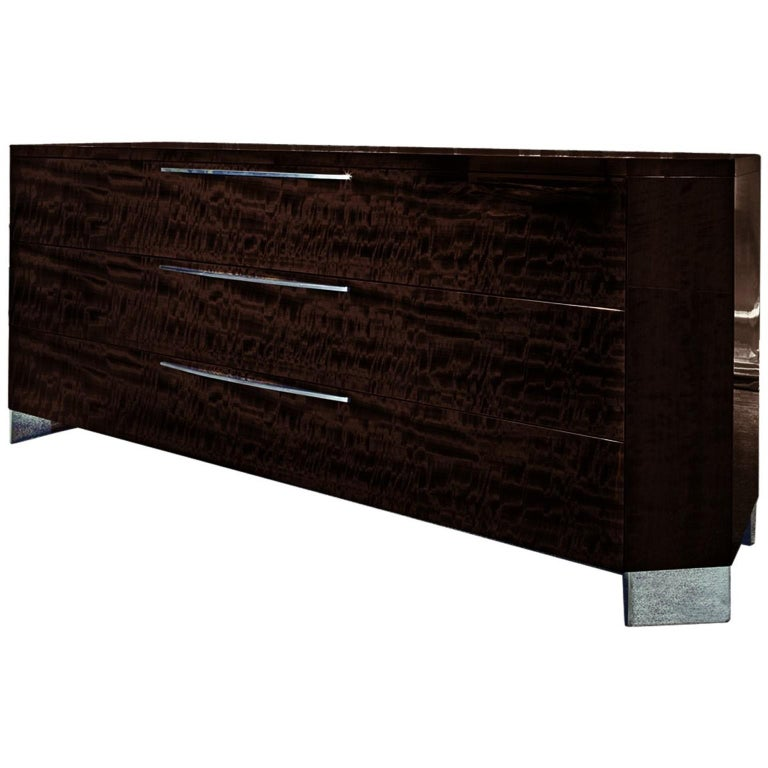 Three-drawer dresser of European curly eucalyptus veneer in a high-gloss finish, inlay top, and chromed stainless steel hardware and feet. Three drawers are full-extension double drawers. Accessories pictured on top of dresser not