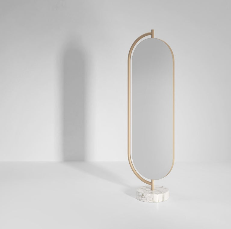Giove is a full length mirror supported by a polished marble base with an elegant metal structure. The back of the mirror can be upholstered in a number of different fabrics. Giove can rotate inside the metal frame, offering new shapes and angles