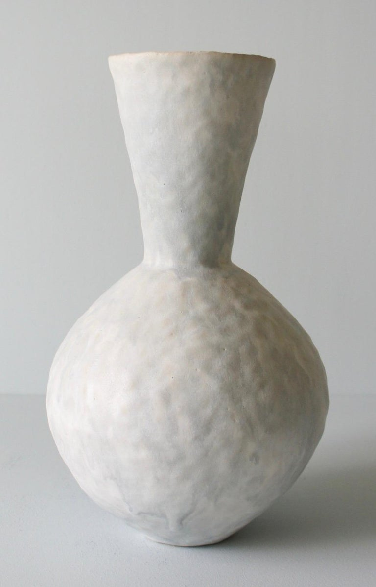 Contemporary American ceramic artist Giselle Hicks' glazed pale grey stoneware vase is part of her Vessel series. Each form is built by hand using a coil and pinch technique. They are formal explorations in shape, volume, color and composition. The