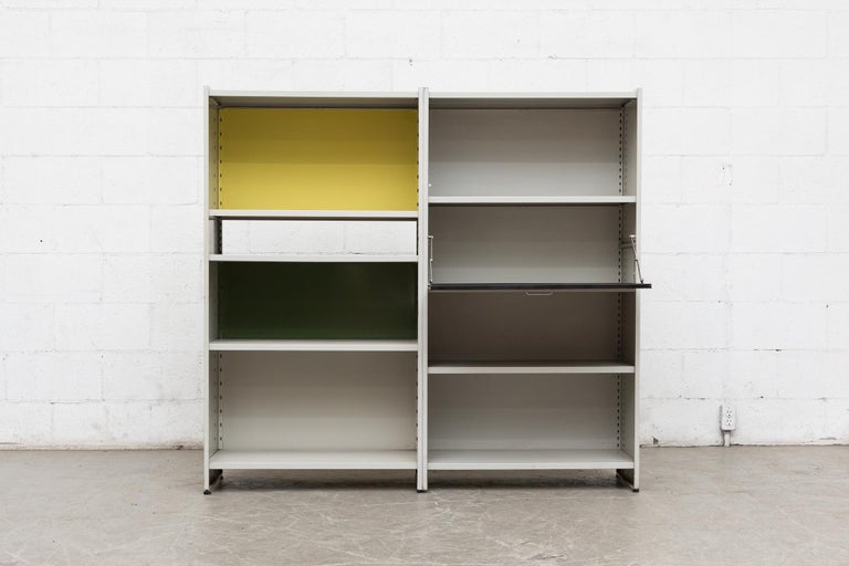 Amazing Gispen 5600 bookshelf by A.R. Cordemeyer. Grey enameled metal two-section industrial bookshelf and storage unit with drop down desk, black, yellow and green enameled metal panels. Can be used as a room divider, beautiful Eames inspired 360