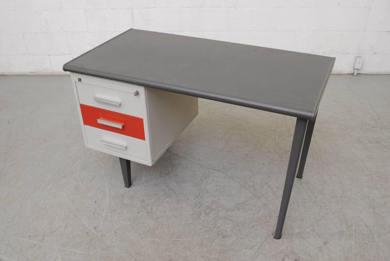 Rare Gispen Industrial desk with red enameled metal drawer and linoleum top. Three sliding drawers. Original condition with visible wear. Has key.