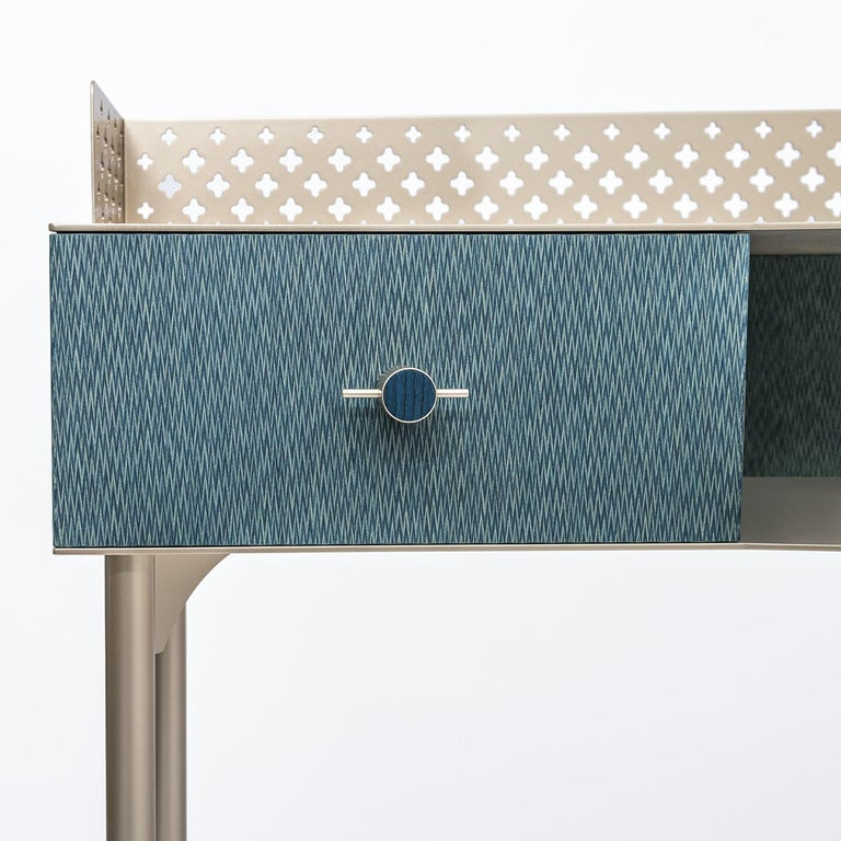 This delicate make-up table is made from wood with a fabric-effect surface. It contains two soft-close drawers with precision-calibrated, metallic handles with wooden inserts. The item is trimmed with hand-finished, laser-cut metallic sheets with a