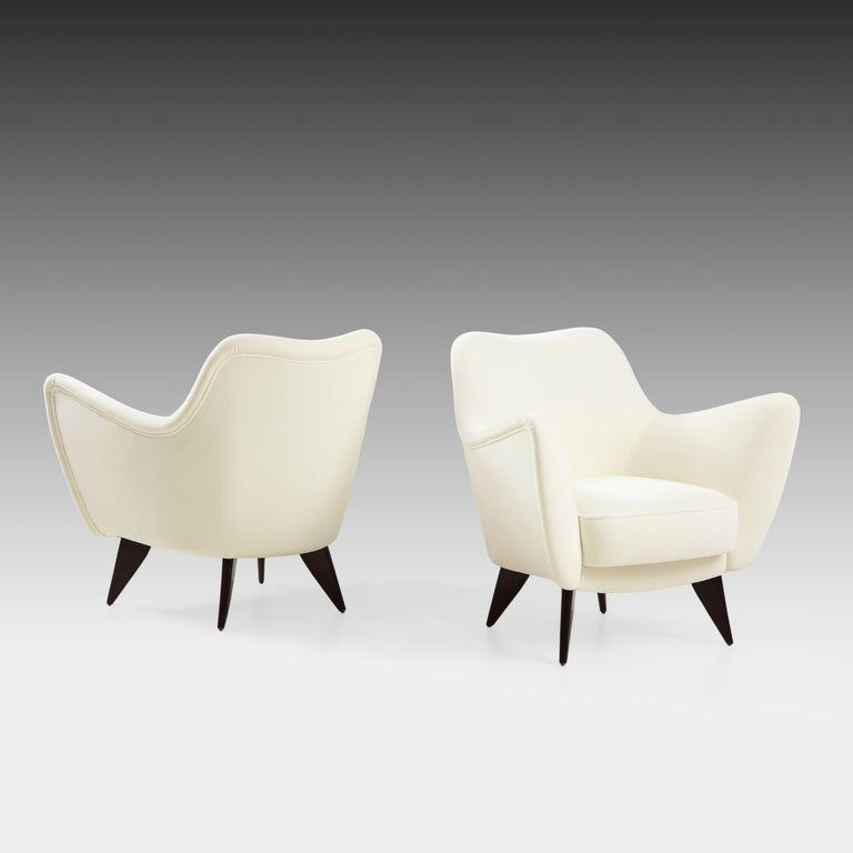 Giulia Veronesi for ISA Bergamo elegant and sculptural ivory velvet pair of 'Perla' armchairs or lounge chairs with slightly curved back and gently outstretched arms ending in signature sharply tapered flat walnut legs, Italy, 1950s. This chic model