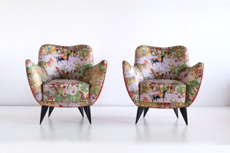This pair of Perla armchairs was designed by Giulia Veronesi and produced by ISA Bergamo, Italy. Its sensual curves and the elegantly tapered legs give the chair a sculptural and modern feel. The armchairs retain their colorful original fabric