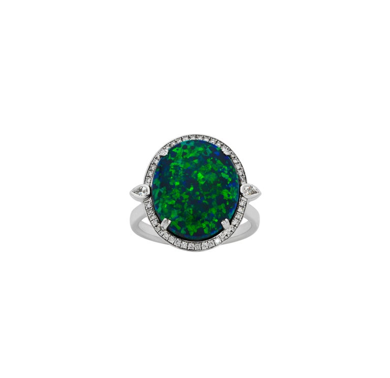 Giulians 18k Art Deco inspired 6.76ct Australian Black Opal and diamond ring.  This ring features a cabochon cut natural solid Black opal, from Lightning Ridge NSW, with deep and bright blue-green play of color.  The opal is surrounded by 38 pave