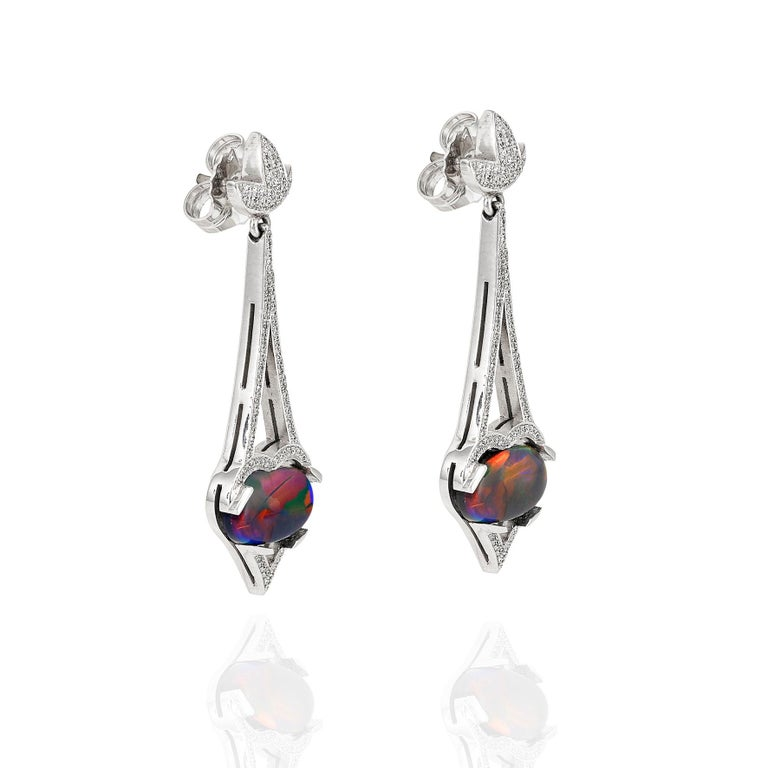 Giulians 18 karat white gold Art Deco inspired black opal and diamond drop earrings.  These earrings feature two oval cabochon, natural, solid Australian opals from Lightning Ridge, NSW (total weight 2=3.70ct).  The opals display deep blue, green