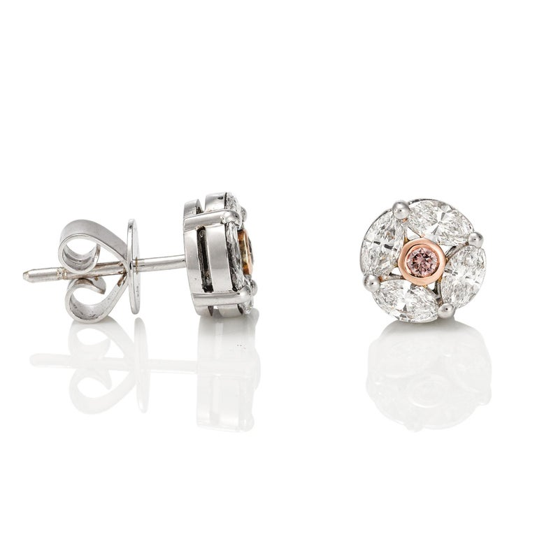Giulians 18 karat rose and white gold diamond earrings.  Each earring features a round brilliant cut 0.05ct pink champagne diamond (PC1 - Si) set in 18 karat rose gold bezel setting.  The pink diamonds are surrounded by a cluster of 8 marquise cut