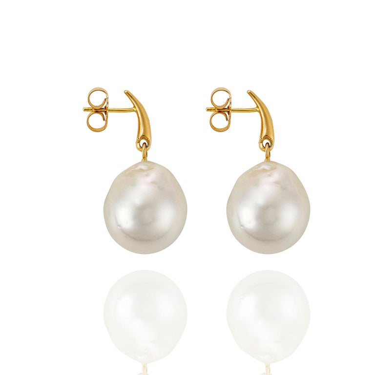 Giulians 18 karat yellow gold Australian South Sea Baroque Pearl Drop Stud Earrings.  Each earring features a large 17.5 - 18mm Cultured South Sea baroque pearl, which articulates from an 18ct yellow gold tapered bar.  The stud posts are located