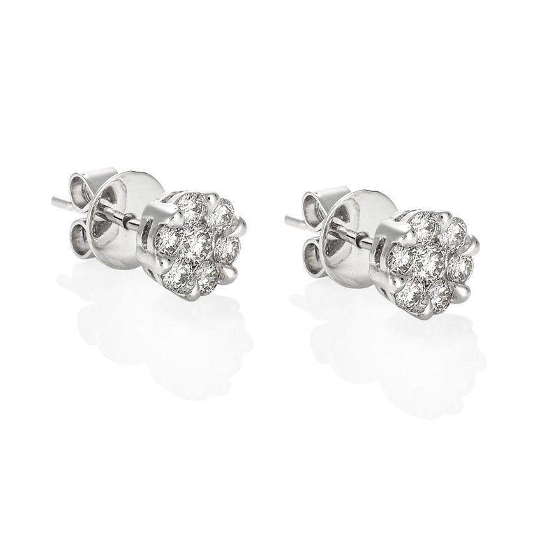 Giulians 18 karat white gold diamond set stud earrings.  Each earring features 6 round brilliant cut diamonds in prong settings and one larger round brilliant cut diamond set in the centre.  The total diamond weight is 14=0.90ct (G-H/VS-Si).  The