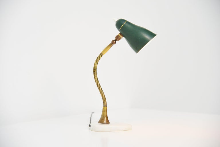 Nice adjustable small table lamp attributed to Giusepp Ostuni and manufactured by Oluce, Italy 1955. The table lamp has a very nice shaped marble base which has a small chip to it. It has a brass bendable arm and a green aluminium shade with on/off