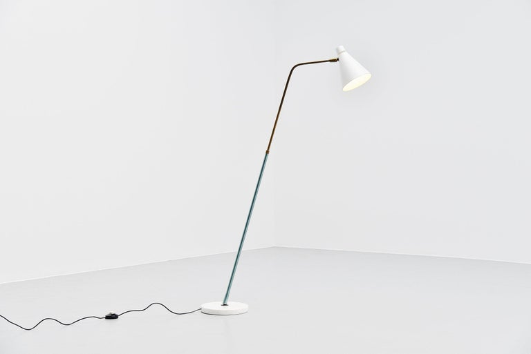 Very nice and sophisticated minimalist extendable floor lamp designed by Giuseppe Ostuni and manufactured by Oluce, Italy 1952. This lamp has a stem that is adjustable in angle and height and the shade is adjustable as well. Very nice solid brass