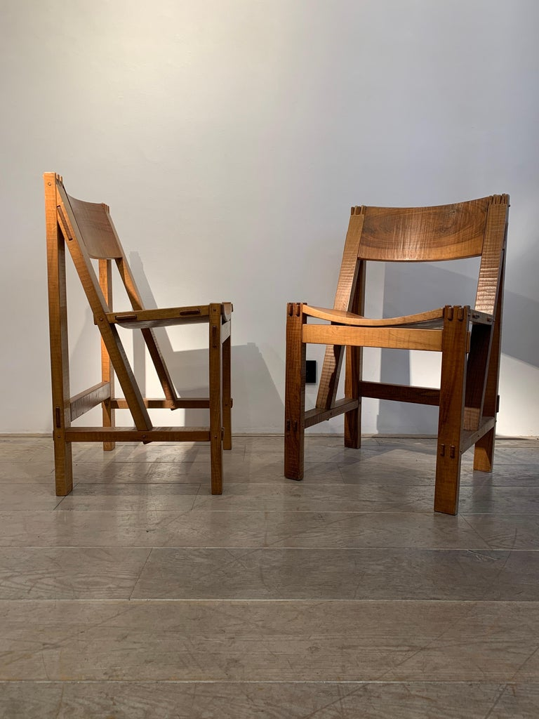 The pair is by Giuseppe Rivadossi. The model is known as the Regina chair. It was designed in 1962 and realized from 1968. The set dates circa 1968-1970s. It is totally handmade in Italian walnut. The architonic style creates emphasis on the