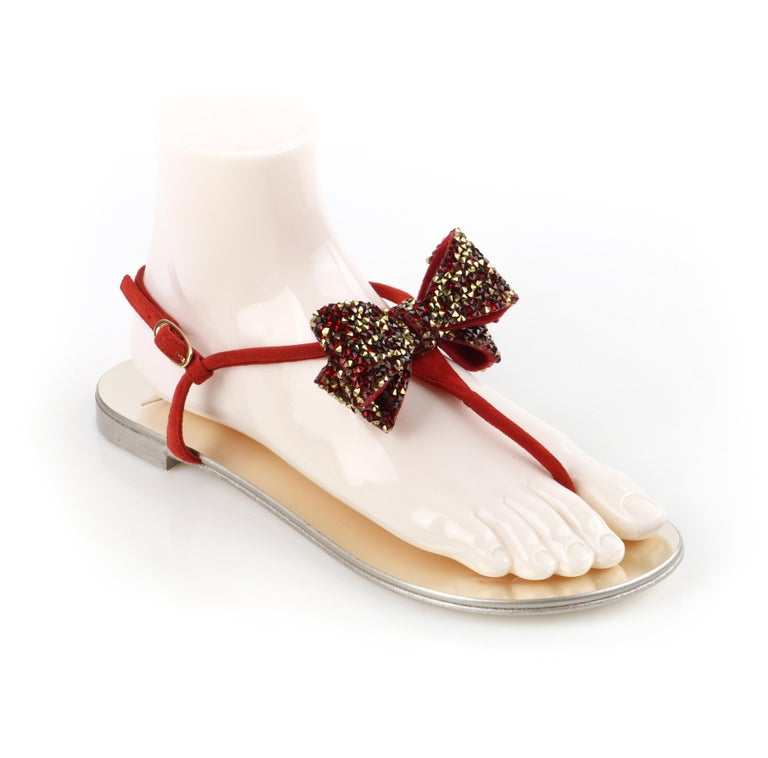 GIUSEPPE ZANOTTI Metallic Leather Suede Jeweled Bow Strap Back Thong Sandals    Brand / Manufacturer: Giuseppe Zanotti Style: Thong sandals  Color(s): Shades of red (strap, crystals); metallic silver (sole); shades of gold (crystals)  Note: The
