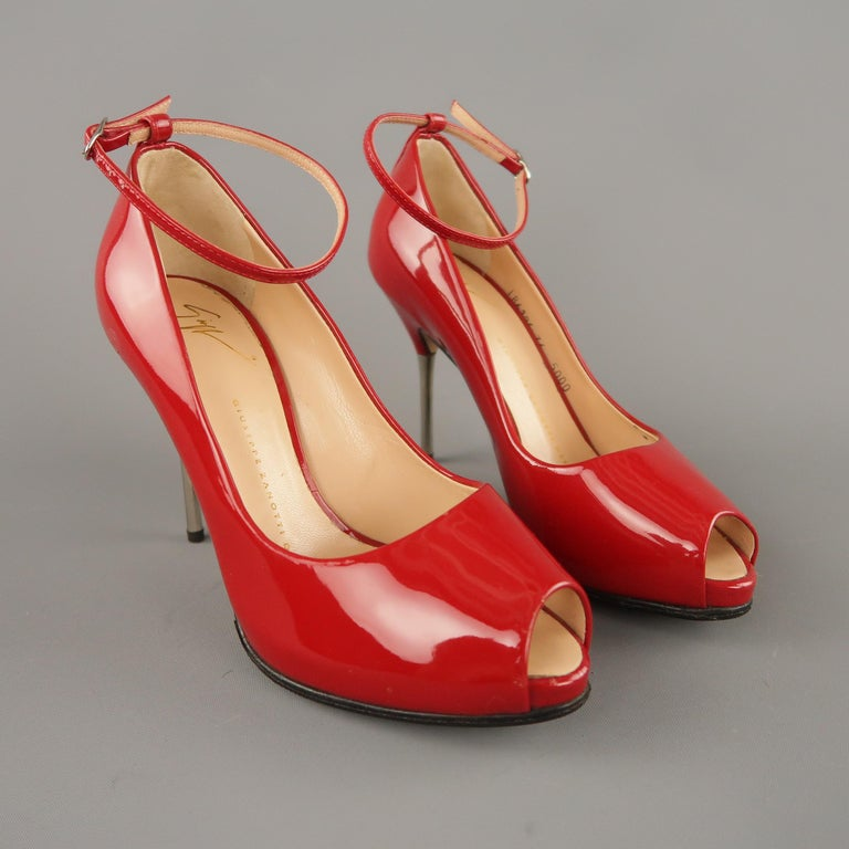 GIUSEPPE ZANOTTI pumps come in red patent leather with a concealed platform peep toe, skinny ankle strap, and silver tone metal spike heel. Made in Italy.  Original retail price $595.00   Excellent Pre-Owned Condition. Marked: IT 36   Measurements: