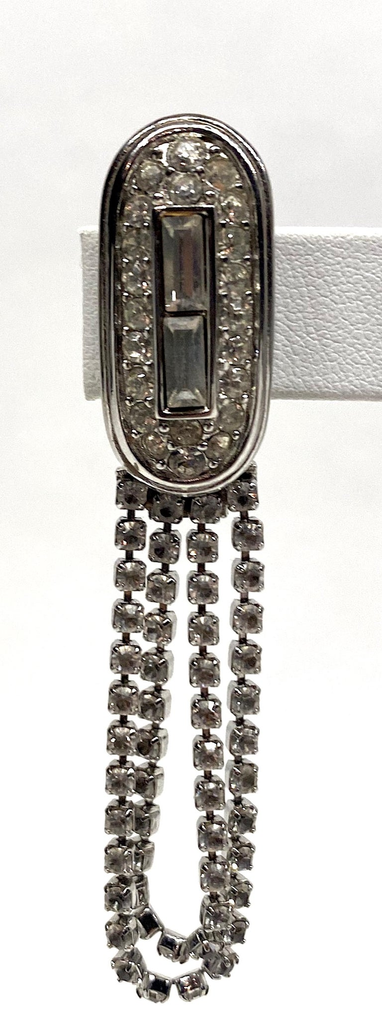 A lovely pair of 1980s Givenchy Art Deco style rhinestone loop fringe earrings in rhodium plate. Each earring is comprised of a .5 of an inch wide and 1.13 of an inch long oval top piece. It is set with two rhinestone baguettes down the center and