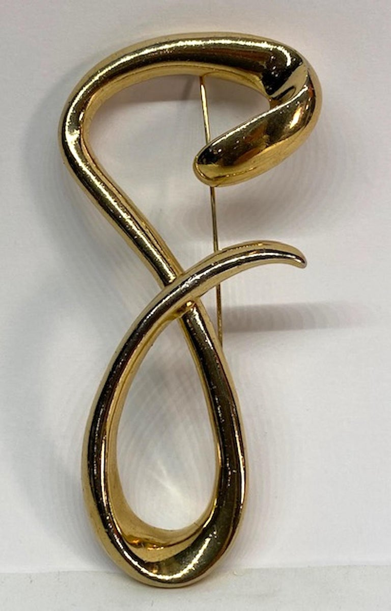A chic 1980s freeform script letter G brooch by Givenchy. The large gold plate brooch measures 2.25 inches at the widest and 4.38 inches tall. The brooch is very three dimensional with the tale of the G overlapping the back part. It is .5 of an inch