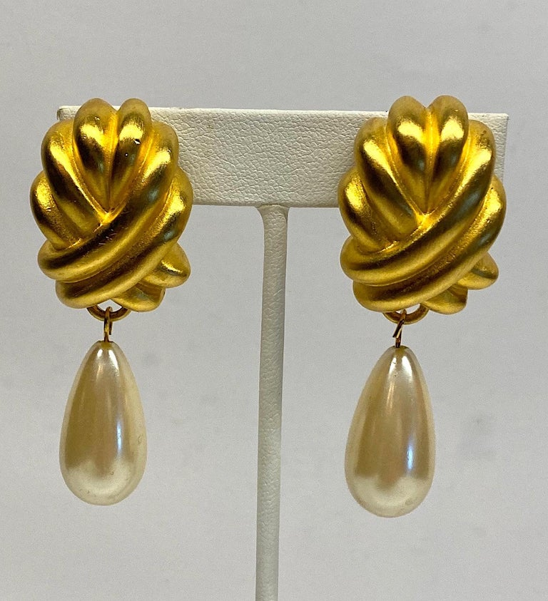 A beautiful pair of Givenchy 1980s large sating gold knots with pear shape faux pearl pendants. Each gold knot is .85 of an inch wide, 2.25 inches long and .5 of an inch deep. Including the 13 x 25 mm pear faux pearl, the earrings are 2.38 inches