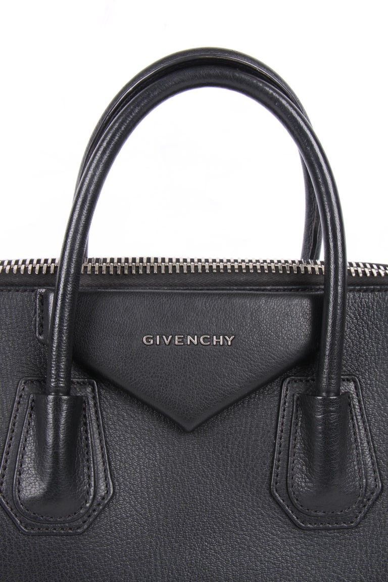 Wonderful basic bag designed by Givenchy wearing the name Antigona, this is size medium.  A trapezoid-shaped model. Crafted from sturdy black leather with silver-tone hardware. Two handles on top and a shoulder strap.  Top closure with a zipper,