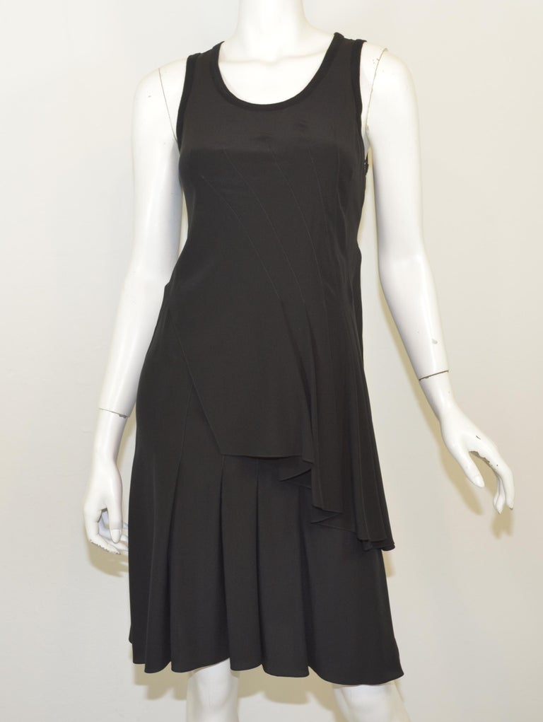Givenchy black dress 100% silk features an asymmetric pleated design throughout with a knit trim collar, and has a side zipper closure. Dress is a size 38, Made in Italy  Measurements: bust 32'', waist 30'', hips 34'', length 39''