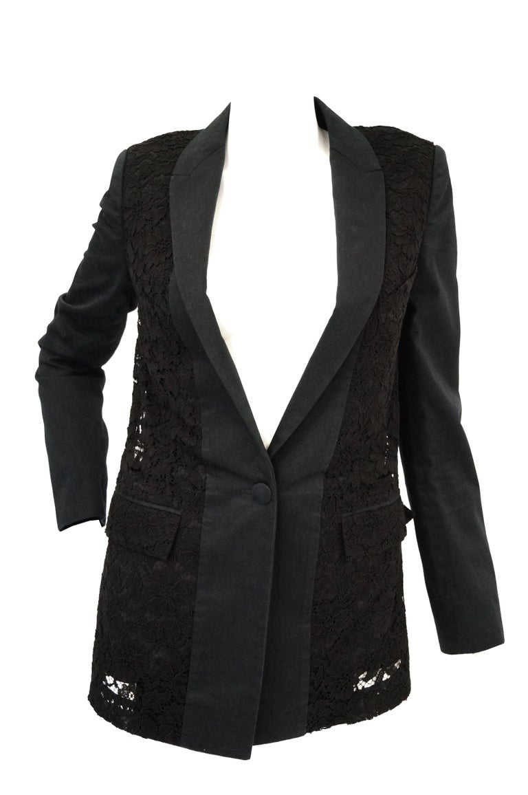 Gorgeous black lace thin lapel longline blazer by Hubert de Givenchy. The blazer features long sleeves, a low neckline with narrow solid black lapels, two pockets, and hit at the waist. The blazer has structured shoulders, and a single button