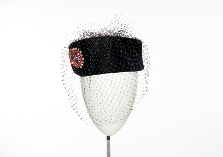 Givenchy, Circa: 1960's black velvet pill box hat with prong-set crystal brooch and black birdcage veil.  Comes with original Givenchy hat box.  Circumference: 24