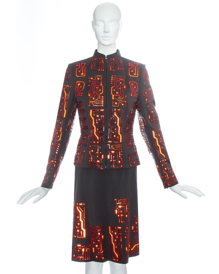 Givenchy by Alexander McQueen; grey wool skirt suit with red reflective plastic appliqués in the form of circuit boards. Zip fastening down centre front, fitted waist and silk lining.   Fall-Winter 1999