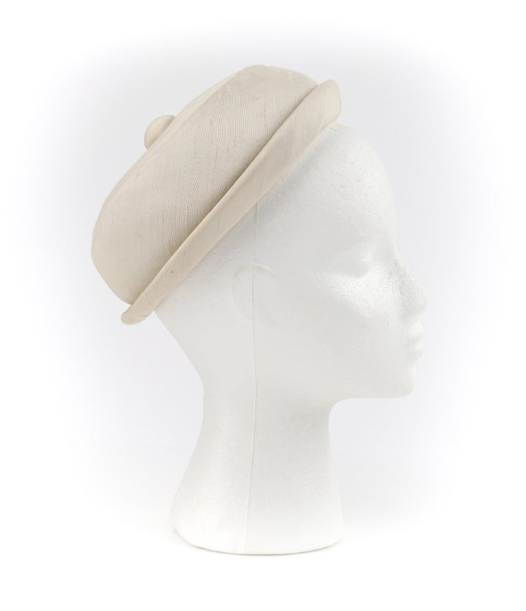 GIVENCHY c.1950's Solid Cream Silk Duponi Pillbox Style Detailed Button Top Hat  Circa: 1950's  Label(s): HUBERT de GIVENCHY PARIS; Saks Fifth Avenue Style: Pillbox Color(s): Cream Lined: Yes  Unmarked Fabric Content (feel of): Exterior: Silk Duponi