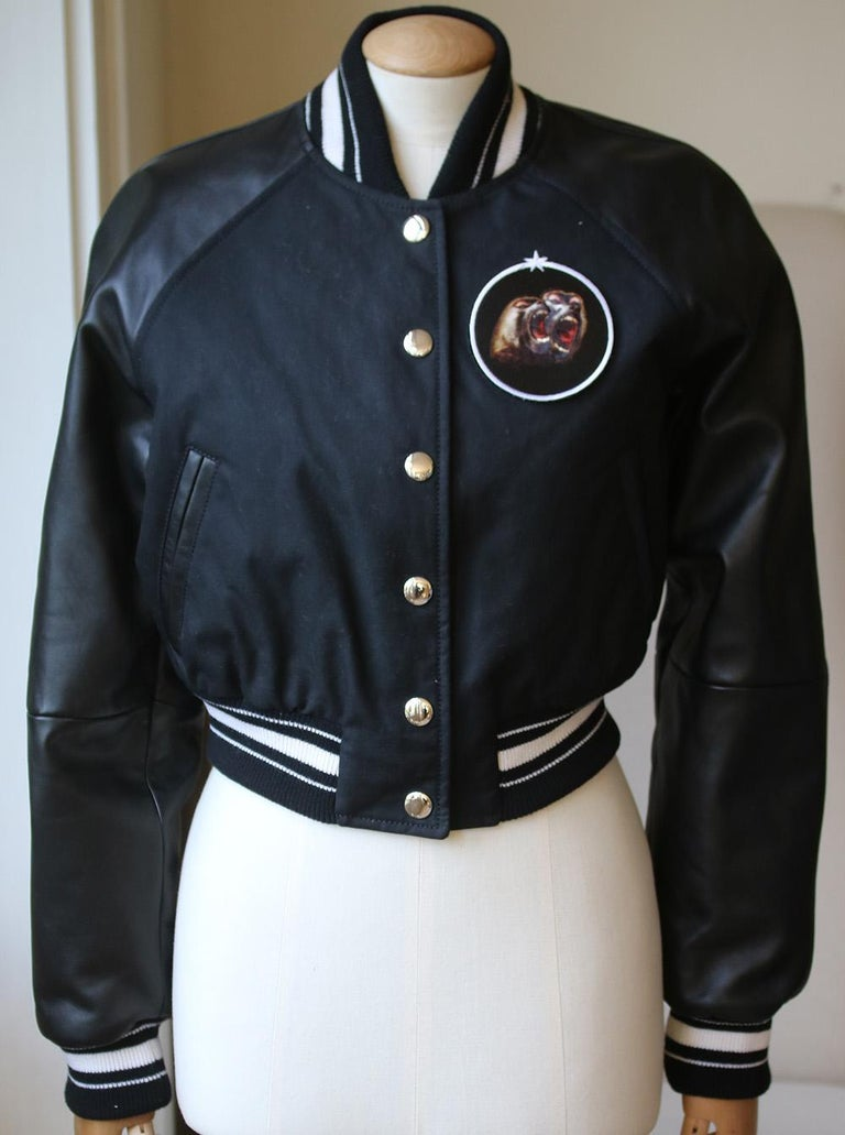 This black cotton, lambskin and wool cropped bomber jacket from Givenchy features a ribbed collar, a snap button closure, long length raglan sleeves, two slanted front pockets, a ribbed hem and cuffs, a full lining, a white striped trim and a