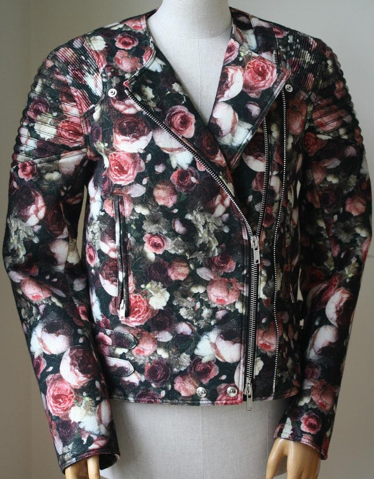 Multi-pink, green and black floral felt wool bomber jacket from Givenchy. Press stud lapels lead into an off-centre zip down front. Structured and ribbed shoulder pads. Long sleeves with exposed and elongated zip cuffs. Two front zip pockets. Double