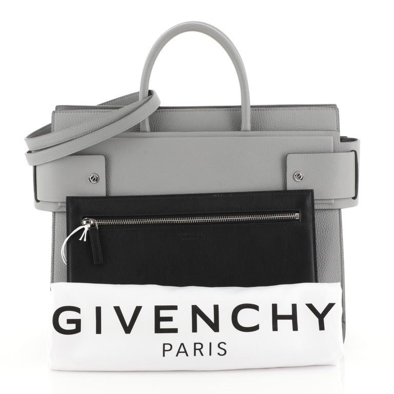 This Givenchy Horizon Satchel Leather Medium, crafted from gray leather, features dual rolled top handles, belted open top with snap sides, embossed logo at front and silver-tone hardware. It opens to a black leather interior.   Estimated Retail