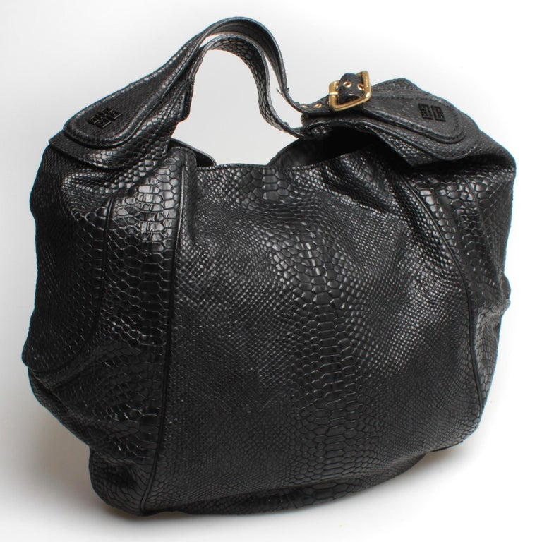 Black snakeskin Givenchy nightingale tote with single strap. Logo embossed leather with light gold toned hardware and fabric lining.