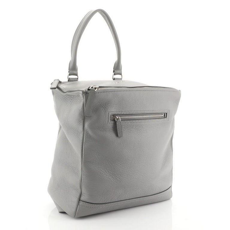 This Givenchy Pandora Backpack Leather, crafted from gray leather, features a leather top handle, adjustable shoulder straps, exterior front zip pocket, and silver-tone hardware. Its top zip closure opens to a black fabric interior with zip and slip