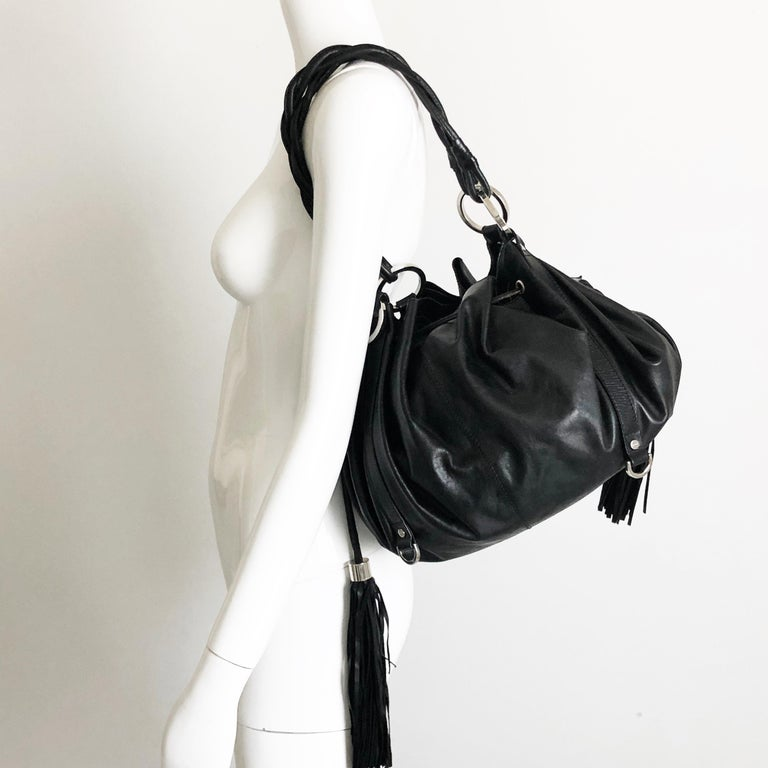 Authentic, preowned Givenchy black leather pumpkin tote or hobo bag, from mid 2000s. Silver hardware/unlined interior w/one attached leather pouch/drawstring closure with tassels. Classic shape & style. Preowned with some signs of prior use & wear: