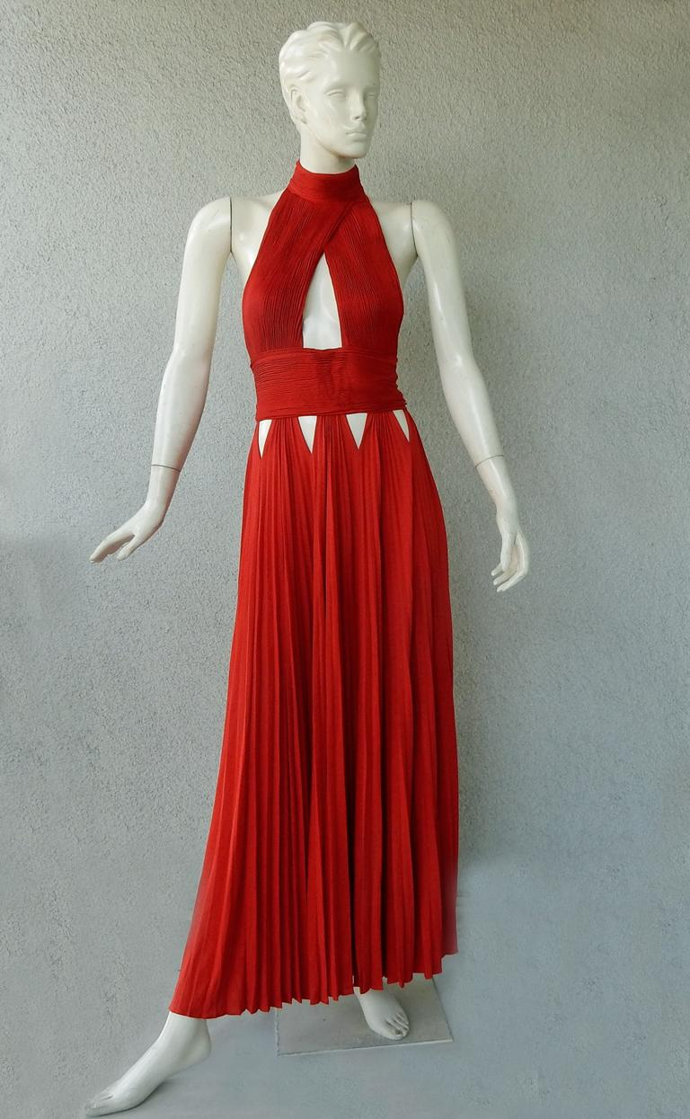 Givenchy red jersey plisse halter evening dress adorned with strategically cut-out panels at hips and bodice.  Pleated skirt drapes easily onto the body.  Open back;  back zipper closure; button neck closure.  Dress has great visual appeal and