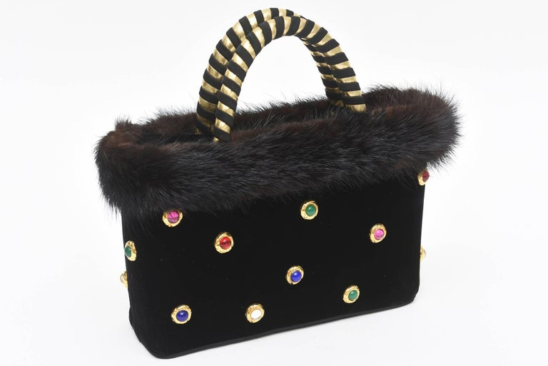 This rare and stellar ensemble set of vintage Givenchy of black doe skin (fine Suede) evening gloves set with colored stones and a velvet matching evening bag set with multi-colored stones will sure make any evening out a conversation place. The bag