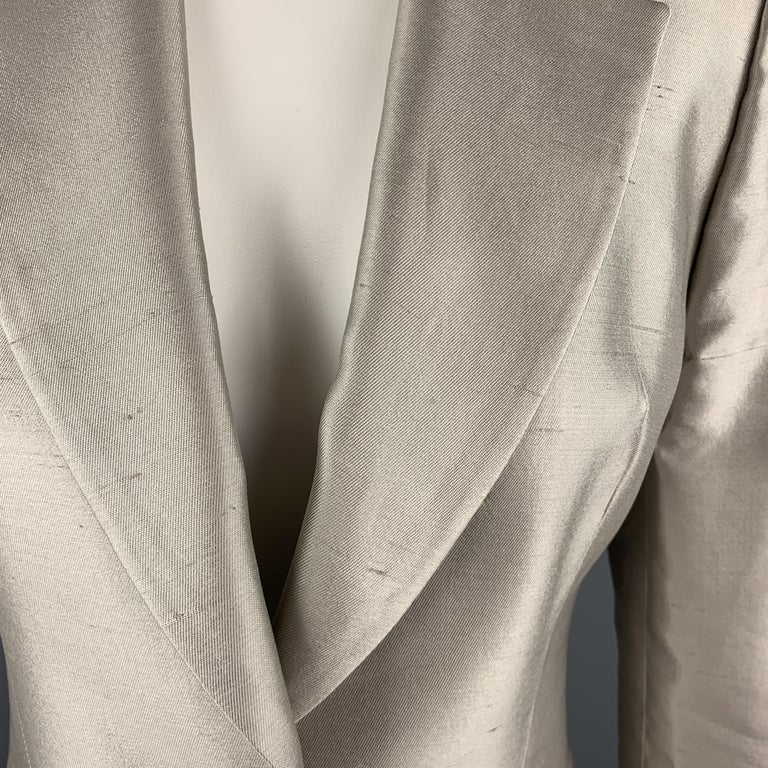 GIVENCHY blazer comes in muted silver silk shangtung with a notch lapel, single button front, cropped hem, and silver tone metal button detailed cuffs. Spot by button. As-is. Made in France.  Good Pre-Owned Condition. Marked: FR