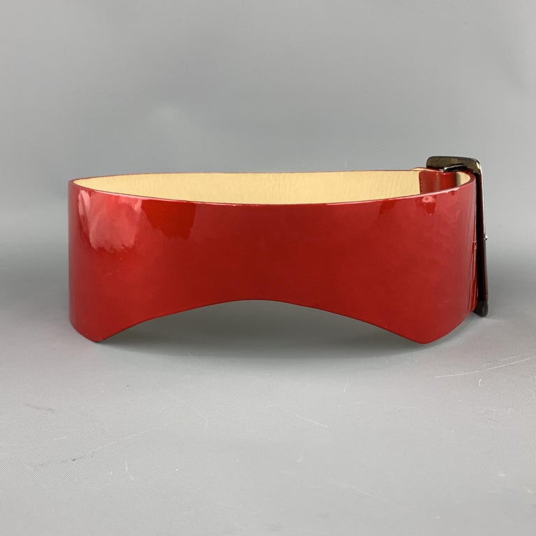 GIVENCHY waist belt features a thick red patent leather strap with side cutouts and dark silver tone metal oversized logo buckle. Made in France.  Very Good Pre-Owned Condition. Marked: S  Length: 30 in. Width: 3 in. Fits: 26-28 in.