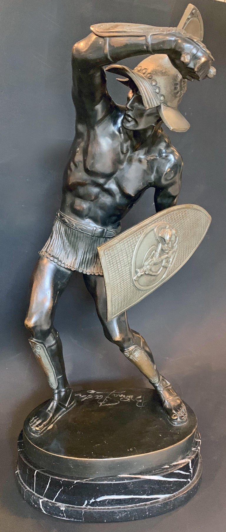 The first example of this sculpture we have seen, this striking depiction of a male gladiator -- clothed in nothing but a short mail skirt - is shown in the midst of battle, one arm raised with dagger in hand, the other holding a shield decorated