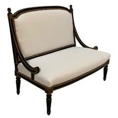 Glamorous Hollywood Regency Ebonized Gilded Settee with White Leather Upholstery