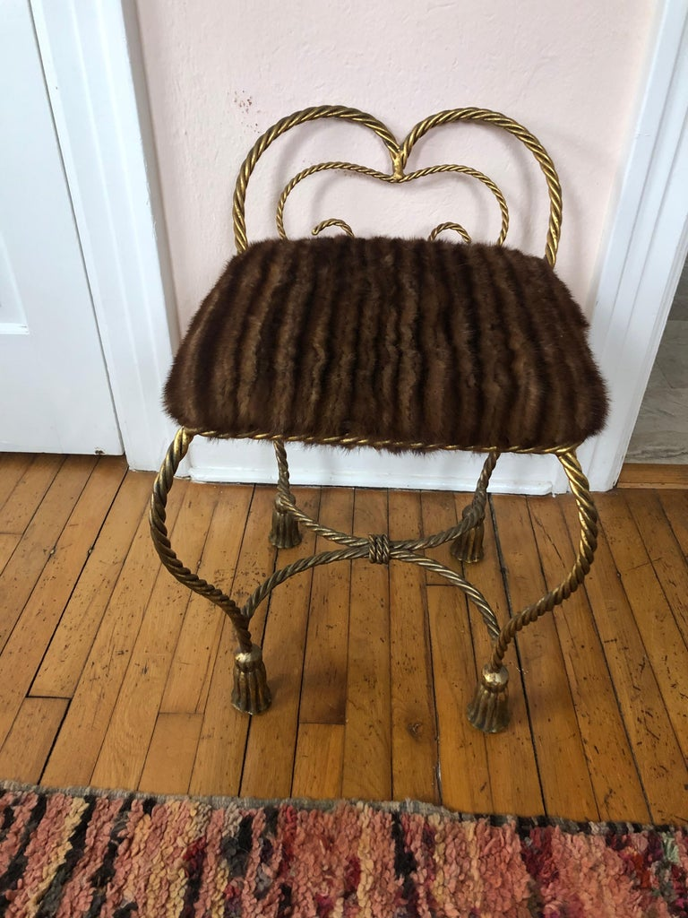 A movie star vintage Italian gilt iron rope and tassel motife boudoir bench or stool, beautifully upholstered in real mink fur. Makes a great little extra seat if used as a floating stool in a living room.