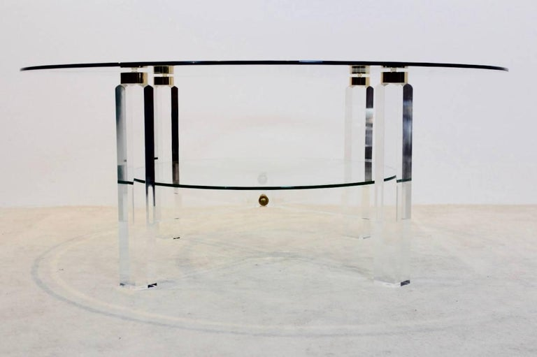 Stunning Belgian coffee table with glamorous performance. The light and glossy Lucite base with beautiful Brass accents has two-tier glass. The table is a unique example of the Hollywood Regency style and in excellent condition.
