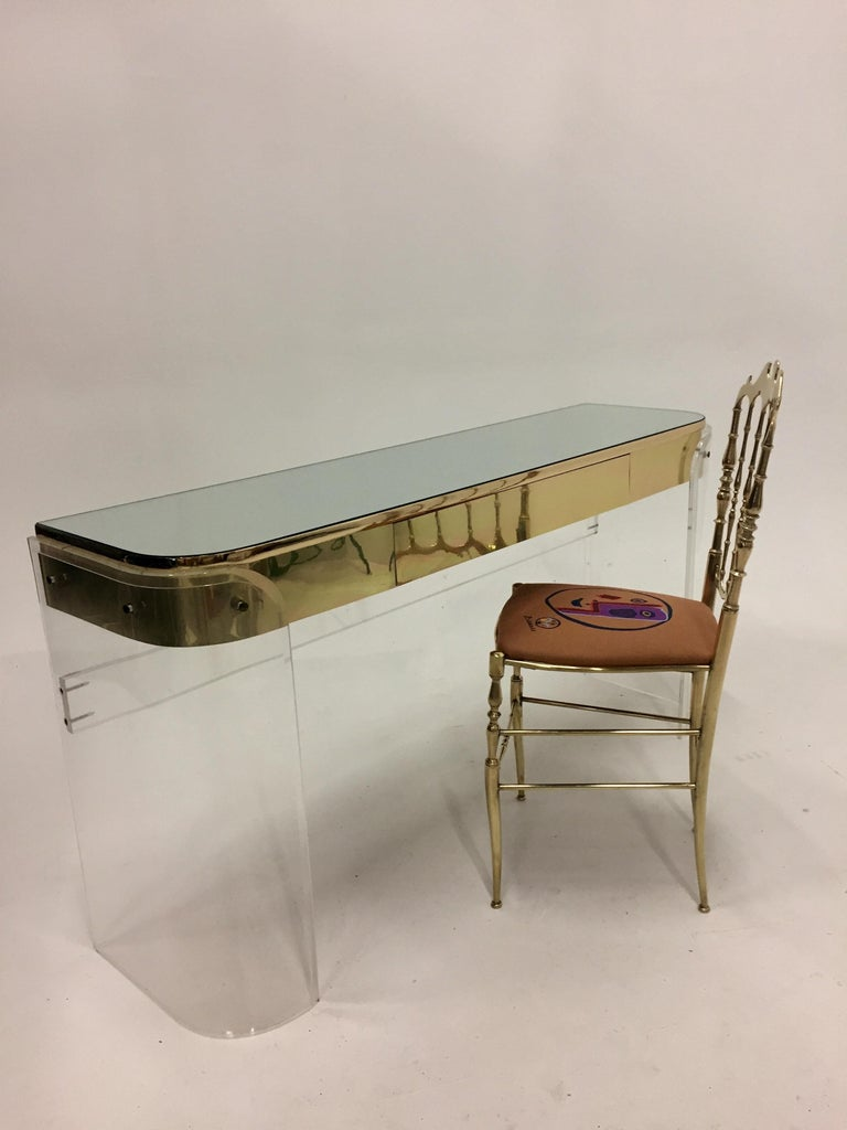 Glamorous Mid-Century Modern Lucite curved vanity or console having gold metal detailing, middle drawer, Lucite stretcher on the back and mirrored top. The space from the floor to the base of the drawer is 24 inches.