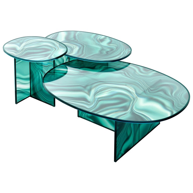 High and low oval-shaped tables in tempered extra light glass, with faded and irregular decoration which takes on the color and veins of marble. The surprising image changing effect makes the veining look dynamic and variable depending on the