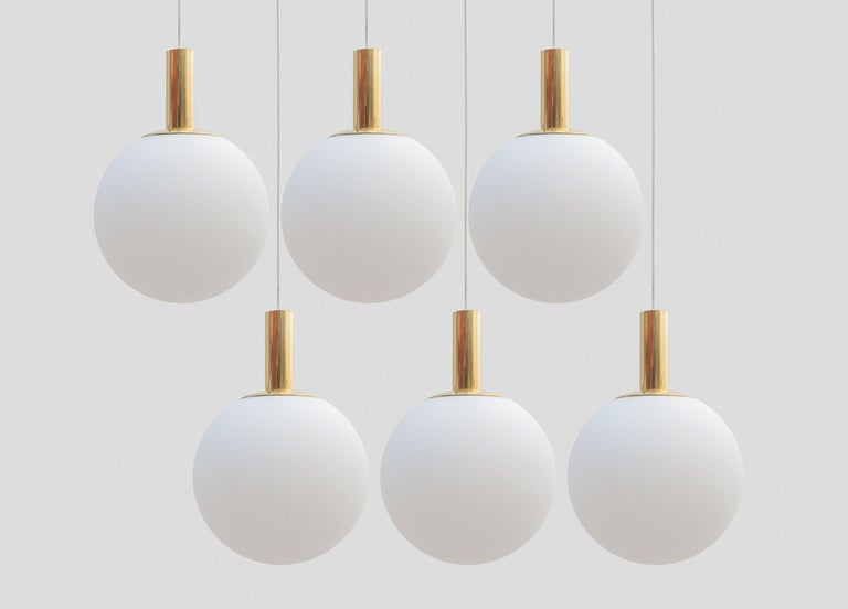 Set of six globe pendant lamps. Classic opal milk glass orb shade with gold tone hardware in a very good condition. Designed by the famous manufacture Limburg Glashütte, Germany.