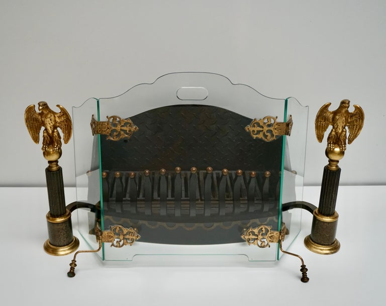 An incredible fire screen of functional art made of green edge glass with brass hinges and feet,