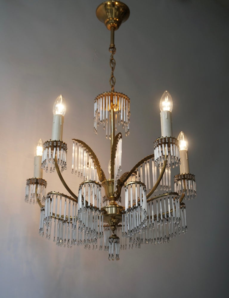 Superb gilt brass chandelier with issuing elegant leaves from which hang glass rods. Glamorous Maison Jansen style brass palm frond chandelier with glass tubes, circa 1950s. Retains warm original patina. Maison Jansen was a Paris based interior