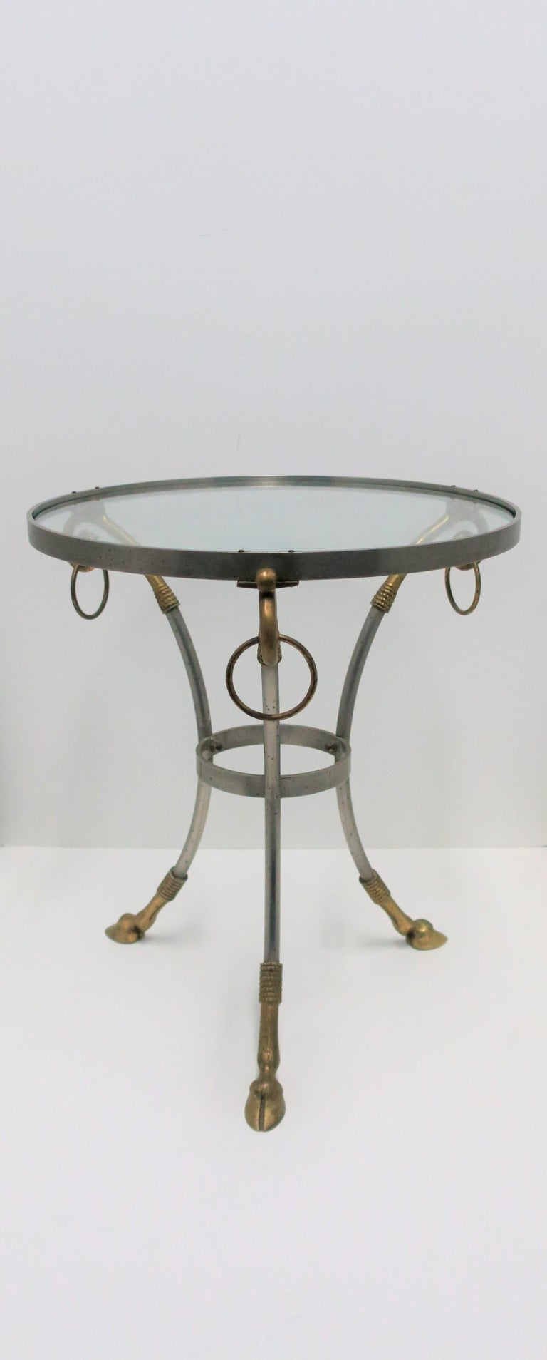 A small and substantial French Gueridon round side or drinks table with brass rams head hoof detailing, in the style of designer Maison Jansen, circa 20th century, France. Table is matte steel and brass - brass loop/ring detail at top,  hoof/legs at