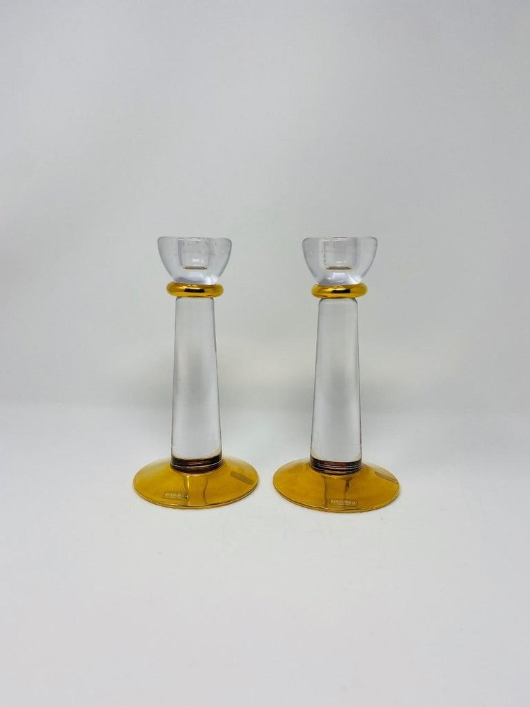 Minimalist and incredibly glamorous pair of Kosta Boda glass candle holders. The pair exhude beautiful lines that can streamline or maximize elegance in your décor. Crystal clear glass accentuated with a gold finish at the base and neck. Both pieces